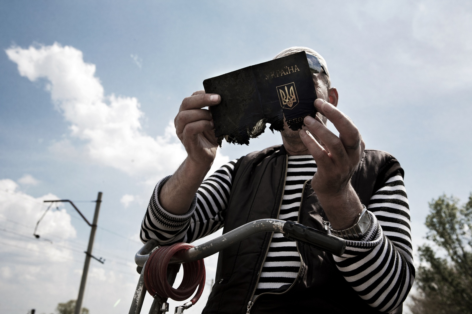 Slavyansk, Andriivka village, Ukraine. May 2014 - A villager looks a Ukrainian passport lost by the rightful owner and found among the remains of a pro-Russian checkpoint, few hours after the end of a clash between separatists and Ukrainian troops. The document, despite being par tially burned, is fully readable. It belonged to a young man coming from the west, from the ranks of the regular army deployed Ukrainian, probably in the National Guard.