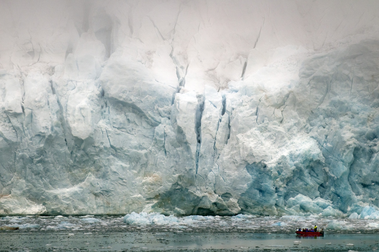 Lacerazioni Polari - Il ghiacciaio si butta nel mare e cadono blocchi con grande fragore dalla sommità nascosta nella nebbia. Un gruppo di visitatori si avvicina in gommone...l'uomo è veramente piccolo di fronte alla natura